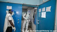 An agent of the National Institute of Public Hygiene (INHP) wearing a personal protective equipment (PPE) suit against the Ebola virus disinfects the premises of the CHU of Cocody following the passage of a first Ebola patient, in Cocody on August 16, 2021. - Ivory Coast began a roll-out of vaccinations against Ebola on August 16, 2021, after the country recorded its first known case of the disease since 1994, the health ministry said. Health workers, close relatives and contacts of the victim were the first to be vaccinated, getting jabs from 5,000 doses sent from Guinea, spokesman Germain Mahan Sehi said. (Photo by Sia KAMBOU / AFP) (Photo by SIA KAMBOU/AFP via Getty Images)
