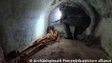 Ein Archäologe untersucht in der versunkenen Stadt Pompeji die mumifizierten Überreste von Marcus Venerius Secundio, einem früheren Sklaven, der nach seiner Freilassung zu Reichtum und damit zu gesellschaftlichem Rang gelangt war. Auf das Grab mit demSkelett stießen die Forscher während Ausgrabungen am Friedhof Porta Sarno im Osten der antiken Römer-Stadt. +++ dpa-Bildfunk +++