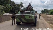 In this image made from video, Mozambican soldiers ride on an armored vehicle in a convoy driving to Mocimboa da Praia, Cabo Delgado province, Mozambique Monday, Aug. 9, 2021. Fresh from recapturing the strategic northern Mozambican port of Mocimboa da Praia held by Islamic extremist rebels for a year, Rwandan and Mozambican troops say they are pursuing the insurgents into the surrounding areas. (AP Photo/Marc Hoogsteyns)