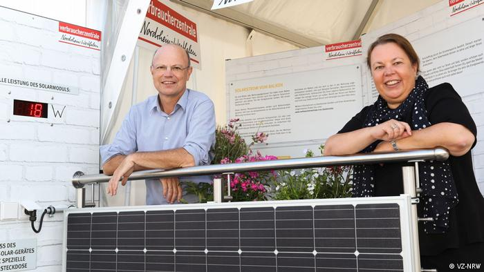 A man and a woman leaning on a railing over plug-in solar panel system