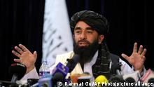 In front of a Taliban flag, Taliban spokesman Zabihullah Mujahid speaks at at his first news conference, in Kabul, Afghanistan, Tuesday, Aug. 17, 2021. For years, Mujahid had been a shadowy figure issuing statements on behalf of the militants. Mujahid vowed Tuesday that the Taliban would respect women's rights, forgive those who resisted them and ensure a secure Afghanistan as part of a publicity blitz aimed at convincing world powers and a fearful population that they have changed. (AP Photo/Rahmat Gul)