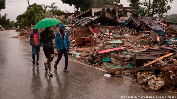 Haitianos paseando bajo la lluvia y junto a casas destruidas por el terremoto
