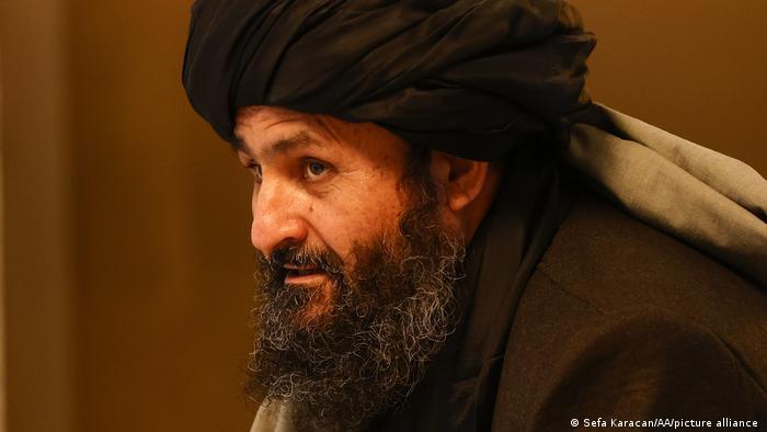 برادر در سال ۱۹۶۸ در ولسوالی دهراوود ولایت ارزگان در جنوب افغانستان متولد شد. او که یکی از چهار بنیانگذار طالبان در سال ۱۹۹۴ است به طایفه درانی، از طوایف پشتون تعلق دارد. برادر در زمان حمله آمریکا به افغانستان معاون وزیر دفاع حکومت طالبان بود. او در سال ۲۰۱۰ در پاکستان دستگیر شد و در سال ۲۰۱۸ به درخواست آمریکا آزاد شد تا نمایندگی طالبان در مذاکرات صلح را برعهده گیرد.