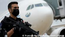 A gendarme guards a government plane carrying people coming from Kabul at the Roissy Charles Gaulle airport, north of Paris, Tuesday, Aug. 17, 2021 in Paris. France evacuated several dozen people from Kabul overnight in a military plane after the Taliban took power in Afghanistan. The flight brought the evacuees to a military air base in Abu Dhabi. Several of the passengers were then sent back to France. (AP Photo/Francois Mori)