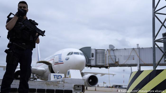 تصویر یک ژاندارم فرانسوی را در حال نگهبانی از هواپیمای دولتی نشان میدهد که از کابل وارد فرودگاه شارل دوگل پاریس شده است. فرانسه پس از خروج اضطراری شهروندان و همکاران محلی از کابل آنها را نخست به فرودگاهی نظامی در ابوظبی اعزام و از آنجا به فرانسه فرستاد.