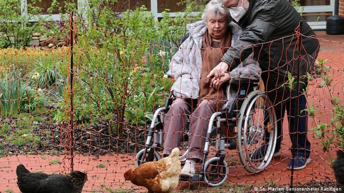 Супружеская пара из дома пристарелых в Ратингене радуется встрече с курами