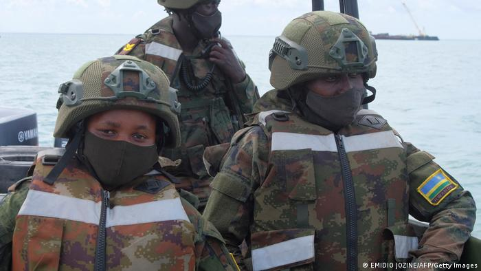 Three Rwandan soldiers on a boat in a Mozambican port