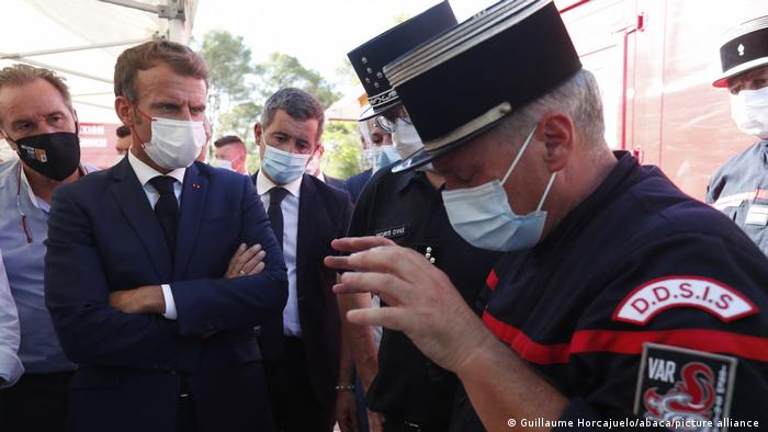 French President Emmanuel Macron (L), speaks with a firefighter officer as he visits the SDIS (Departmental fire and rescue service) and firefighters headquarter in Le Luc, near Saint-Tropez,