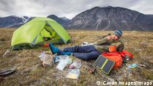 Climber eats meal, relaxes, charges devices at campsite. Pangnirtung, NU, Canada PUBLICATIONxINxGERxSUIxAUTxONLY CRJDIP200331-320792-01,model released, Symbolfoto