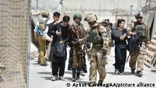 KABUL, AFGHANISTAN - AUGUST 18: Soldiers help a women, fell due to high temperature at the Kabul International Airport as thousands of Afghans rush to flee the Afghan capital of Kabul, on August 18, 2021. Aykut Karadag / Anadolu Agency