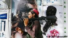 A Taliban fighter walks past a beauty saloon with images of women defaced using a spray paint in Shar-e-Naw in Kabul on August 18, 2021. (Photo by Wakil KOHSAR / AFP)