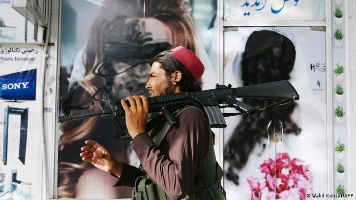 Afghanistan, Kabul   Ein Taliban-Kämpfer läuft an einem Kosmetikstudio vorbei