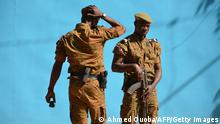 Burkinabe men patrol the army's headquarters from the roof in Ouagadougou on March 3, 2018 a day after dozens of people were killed in twin attacks on the French embassy and the country's military. Eight soldiers died and 12 were seriously wounded in twin attacks on the Burkina Faso military HQ and the French embassy in Ouagadougou, a French security source said on March 3. Eight attackers were also killed in Friday's bloody assault. A previous toll from French security sources had reported at least 28 deaths. / AFP PHOTO / Ahmed OUOBA (Photo credit should read AHMED OUOBA/AFP via Getty Images)