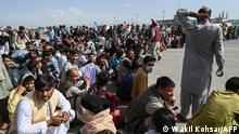 TOPSHOT - Afghan passengers sit as they wait to leave the Kabul airport in Kabul on August 16, 2021, after a stunningly swift end to Afghanistan's 20-year war, as thousands of people mobbed the city's airport trying to flee the group's feared hardline brand of Islamist rule. (Photo by Wakil Kohsar / AFP)