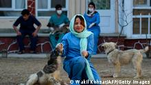 In this photograph taken on February 25, 2020 Head Veterinarian Tahera Rezai, 30, plays with dogs in the courtyard of the Kabul Small Animal Clinic in Kabul. - As US troops prepare to leave Afghanistan, opening the door for a potential Taliban comeback, women across the war-torn country are nervous about losing their hard-won freedoms in the pursuit of peace. The militants were in power for around five years until the US invasion of 2001. They ruled Afghanistan with an iron fist that turned women into virtual prisoners under a strict interpretation of sharia law. (Photo by WAKIL KOHSAR / AFP) / TO GO WITH PROFILE 'AFGHANISTAN-CONFLICT-GENDER' (Photo by WAKIL KOHSAR/AFP via Getty Images)