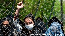 TOPSHOT - A women wearing a facemask peeks from a iron fence as they wait to receive free wheat from the government emergency committee during a government-imposed lockdown on the capital city as a preventive measure against the COVID-19 coronavirus, in Kabul on April 21, 2020. (Photo by WAKIL KOHSAR / AFP) (Photo by WAKIL KOHSAR/AFP via Getty Images)