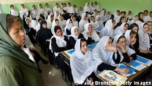 KABUL, AFGHANISTAN - OCTOBER 4: Afghan female students at the Rukhshana high school listen to a IFES (International Foundation For Election Systems) instructor who is teach them about the election process October 4, 2004 in Kabul, Afghanistan. IFES is an NGO (non governmental organization) that is jointly funded by the U.S.AID and Canada who has educated over 300,000 men and women about the upcoming elections. On Saturday, October 9, Afghans will have the chance to vote for the first time in a direct election choosing a presidential candidate. The election is seen as a crucial step towards democracy and peace in the war-torn country after the fall of the Taliban. (Photo by Paula Bronstein/Getty Images)
