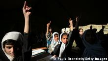 KABUL-AFGHANISTAN-NOVEMBER 22: Afghan girls raise their hands during english class at the Bibi Mahroo high school in Kabul, Afghanistan November 22, 2006. The overcrowded school is made up of UNICEF supplied tents and war torn buildings as it patiently waits for the new building to open next year for its 6,200 students, ranging from ages 7-18, mostly all are females. To accommodate all the students in the limited space there are 3 sessions of classes through out the day. Five years after the fall of the Taliban millions of students have returned to packed schools, making education one of the few success stories in the struggle for a peaceful Afghanistan. (Photo by Paula Bronstein /Getty Images)