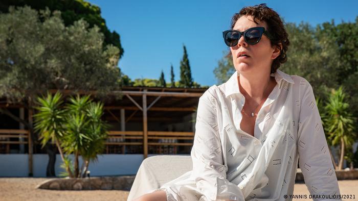 Cena do filme com mulher de óculos e camisa branca sentada em cadeira na praia