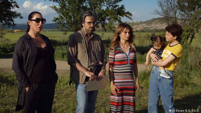 Cena do filme Mães Paralelas. Três mulheres e um homem numa cena externa em meio à natureza. Uma das mulheres segura um bebê