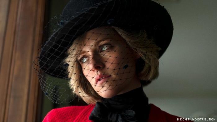 Cena do filme Spencer com a atriz Kristen Stewart interpretando Lady Di, vestindo um casaco vermelho e um chapéu com véu, olhando através de uma janela