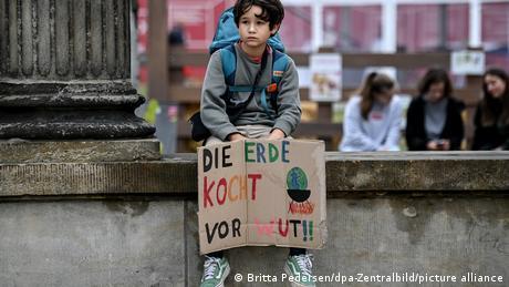Ein kleiner Junge sitzt auf einer Mauer und hält ein Plakat mit der Aufschrift Die Erde kocht vor Wut in der Hand Potsdam   Fridays for Future Klimaprotest