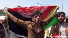 A man holds the flag of Afghanistan during a protest in Jalalabad on Wednesday, Aug. 18, 2021. Taliban militants have attacked protesters in eastern Afghanistan who dared to take down their banner and replace it with the country's flag. At least one person was killed in the attack that fueled fears about how the insurgents would govern this fractious nation. (AP Photo)