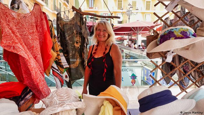 Spain, Mallorca | Marion Kell at her market stand selling clothes and hats