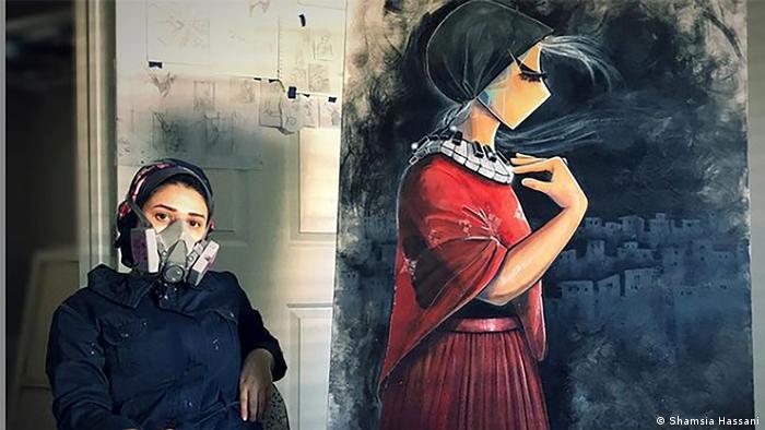 Mulher com máscara respiratória ao lado de enorme grafite de mulher com roupas vermelhas e lenço preto na cabeça
