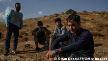 Afghan migrants rest while waiting for transport by smugglers after crossing the Iran-Turkish border on August 15, 2021 in Tatvan, on the western shores of Lake Van, eastern Turkey. - The latest chaos in Afghanistan sparked by the recent gains of territory by the Taliban including the takeover of the capital Kabul has raised fresh alarm over an influx of migrants into Turkey through the Iranian border. Turkey, which shares a 534 kilometre (331 miles) border with Iran, has beefed up its frontier and started building a 243 kilometre wall in a bid to prevent any passage of illegal migrants. (Photo by Ozan KOSE / AFP) (Photo by OZAN KOSE/AFP via Getty Images)