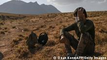 TOPSHOT - An Afghan migrant rests while waiting for transport by smugglers after crossing the Iran-Turkish border on August 15, 2021 in Tatvan, on the western shores of Lake Van, eastern Turkey. - The latest chaos in Afghanistan sparked by the recent gains of territory by the Taliban including the takeover of the capital Kabul has raised fresh alarm over an influx of migrants into Turkey through the Iranian border. Turkey, which shares a 534 kilometre (331 miles) border with Iran, has beefed up its frontier and started building a 243 kilometre wall in a bid to prevent any passage of illegal migrants. (Photo by Ozan KOSE / AFP) (Photo by OZAN KOSE/AFP via Getty Images)