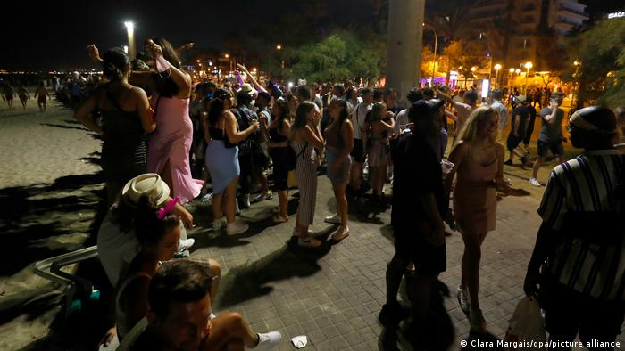 Spain | Mallorca | people gathered at night for an impromptu open-air party
