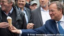 Armin Laschet, Kanzlerkandidat der Union und Vorsitzender der CDU, reicht sein Eis in der Waffel an eine Person im Rahmen seiner Wahlkampftour durch die Osnabrücker Altstadt. +++ dpa-Bildfunk +++