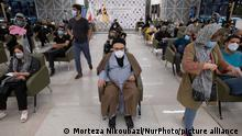 An Iranian cleric and people wait to receive a dose of a new coronavirus disease vaccine during the mass general COVID-19 vaccination in the Iran Grand Bazaar, Iran Mall, in western Tehran, August 17, 2021. (Photo by Morteza Nikoubazl/NurPhoto)