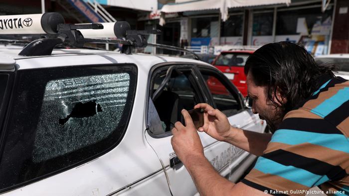 Journalist in Afghanistan filmt mit dem Handy in ein zerschossenes Auto hinein