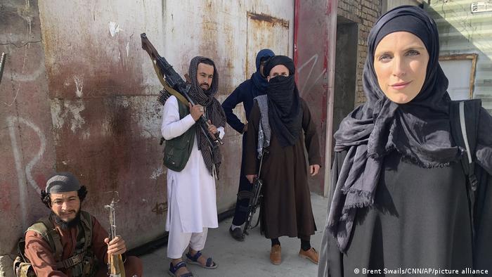 Afghanistan | CNN-Reporterin Clarissa Ward in Kabul verschleiert mit freiem Gesicht, im Hintergrund vier Männer mit Gewehren