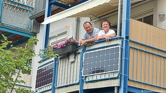 A couple looks over a balcony where a mini solar panel system has been installed