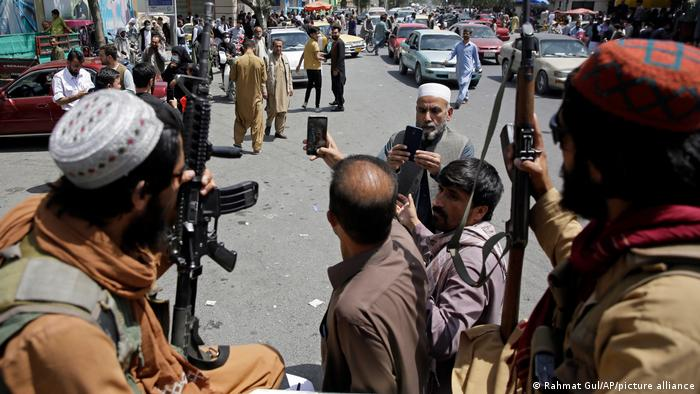Afghans take selfie with Taliban fighters during patrol in the city of Kabul, Afghanistan, Thursday, Aug. 19, 2021.