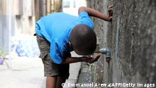 A boy drinks from a public tap in Lagos on March 19, 2015. Without reforms, the world will be plunged into a water crisis that could be crippling for hot, dry countries, the United Nations warned. In an annual report, the UN said abuse of water was now so great that on current trends, the world will face a 40-percent global water deficit by 2030 -- the gap between demand for water and the natural replenishment of it. AFP PHOTO/AREWA EMMANUEL / AFP PHOTO / Emmanuel AREWA (Photo credit should read EMMANUEL AREWA/AFP via Getty Images)