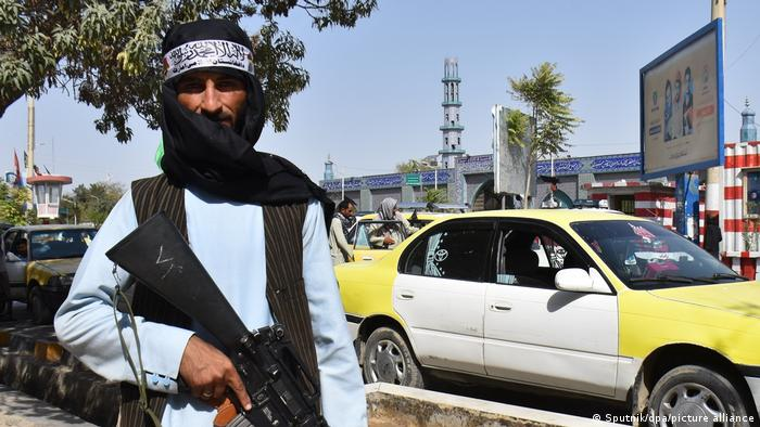 A Taliban militant holds a rifle while standing on a street in Mazar-i-Sharif, Afghanistan