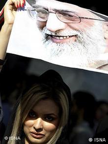 دختری با پوشش مدرن و پوستر آیتالله خامنهای در دست