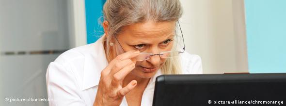 A woman with gray hair and glasses works at a laptop