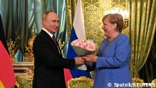 Russian President Vladimir Putin presents flowers to German Chancellor Angela Merkel during their meeting at the Kremlin in Moscow, Russia August 20, 2021. Sputnik/Kremlin via REUTERS ATTENTION EDITORS - THIS IMAGE WAS PROVIDED BY A THIRD PARTY.