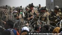 US soldiers stand guard behind barbed wire as Afghans sit on a roadside near the military part of the airport in Kabul on August 20, 2021, hoping to flee from the country after the Taliban's military takeover of Afghanistan. (Photo by Wakil KOHSAR / AFP) (Photo by WAKIL KOHSAR/AFP via Getty Images)