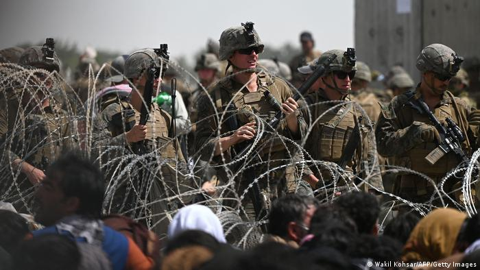 US soldiers stand guard behind barbed wire as Afghans sit on a roadside near the military part of the Kabul airport