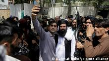 An Afghan takes a selfie with Taliban fighters on patrol in Kabul, Afghanistan, Thursday, Aug. 19, 2021. The Taliban celebrated Afghanistan's Independence Day on Thursday by declaring they beat the United States, but challenges to their rule ranging from running a country severely short on cash and bureaucrats to potentially facing an armed opposition began to emerge. (AP Photo/Rahmat Gul)