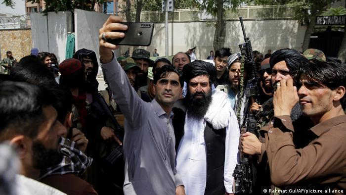 أفغاني يلتقط صورة سيلفي مع مقاتلي طالبان في جولة في كابول ، أفغانستان.