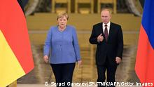 Russian President Vladimir Putin (R) and German Chancellor Angela Merkel walk to attend a press conference after their talks at the Kremlin in Moscow on August 20, 2021. - The trip will be the 20th and last visit to Russia for Angela Merkel as German Chancellor, who bows out of politics following an election in Germany on September 26, 2021. (Photo by Sergei GUNEYEV / SPUTNIK / AFP) (Photo by SERGEI GUNEYEV/SPUTNIK/AFP via Getty Images)