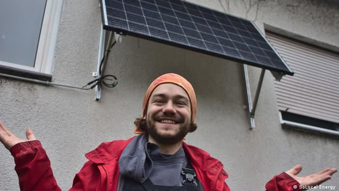 A man standing under a small solar panel mounted to the wall of a building