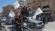 Members of Syria's top jihadist group the Hayat Tahrir al-Sham (HTS) alliance, led by al-Qaeda's former Syria affiliate, parade with their flags and those of the Taliban's declared Islamic Emirate of Afghanistan through the rebel-held northwestern city of Idlib on August 20, 2021. - The armed group that formally broke ties with al-Qaeda years ago is considered to be the most prominent jihadist group in Syria after a decade of war. HTS controls nearly half of the Idlib region -- the last remaining opposition bastion in Syria -- alongside other less influential groups. (Photo by OMAR HAJ KADOUR / AFP) (Photo by OMAR HAJ KADOUR/AFP via Getty Images)